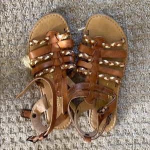 Brown gladiator sandals with gold accents